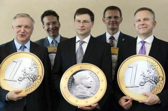 Olli Rehn, Vice-President of the European Commission responsible for Finance and the euro, Jeroen Dijsselbloem, president of Eurogroup, Valdis Dombrovskis, Latvian Prime Minister, Andris Vilks, Latvian Minister for Finance, and Ilmārs Rimšēvičs, Governor of the Bank of Latvia, all holding giant false 1 Euro coins at the effigy of Latvia (from left to right). (EC Audiovisual Services, 09/07/2013).