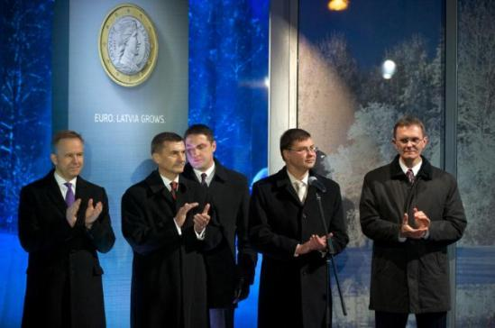 """Ilmārs Rimšēvičs, Governor of the Bank of Latvia, Andrus Ansip, Estonian Prime Minister, Valdis Dombrovskis Latvian Prime Minister and Andris Vilks, Latvian Minister for Finance, all applauding, at midnight of 31 December 2013. The next minute Latvia joined the Eurozone. They all stand next to a poster with a 1-euro coin and the inscription """"Euro. Latvia grows."""" (in the foreground, from left to right). (EC Audiovisual Services)."""