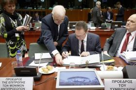 Ioannis Stournaras, Greek Minister for Finance and President of the ECOFIN Council signs documents. (Council of the European Union photographic library, 18/2/2014).
