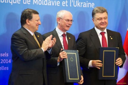 Petro Poroshenko, President of Ukraine (on the right) and Herman van Rompuy, President of the European Council both hold the Association Agreements signed between EU and Ukraine. José Manuel Barroso, President of the European Commission (on the left) applauds. (EC Audiovisual Services, 27/06/2014).