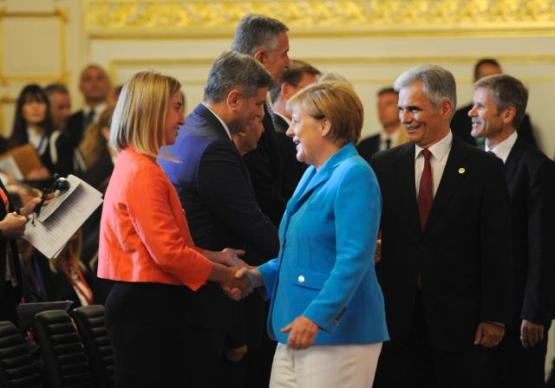 Handshake between Angela Merkel, German Federal Chancellor, in the centre, and Federica Mogherini, on the left, in the presence of Werner Faymann, Austrian Federal Chancellor, on the right (in the foreground) at the Western Balkans Summit 2015 in Vienna, Austria (EC Audiovisual Services, 28/08/2015)