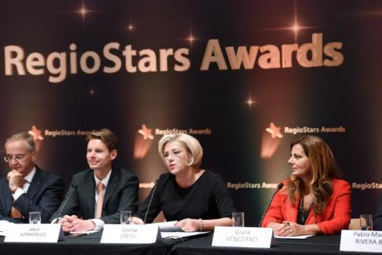 'RegioStars' Awards ceremony 2015. The RegioStars awards honor Europe's most inspirational and innovative regional projects supported by EU Cohesion Policy Funds. An independent RegioStars Awards Jury, chaired by Lambert Van Nistelrooij, Member of the EP, selected 17 finalists from 143 entries and four winners. From left to right: Lambert van Nistelrooij, Jakub Adamowicz, Spokesperson of the European Commission, Corina Creţu, Member of the EC in charge of Regional Policy and Giulia Veneziano, Italian winner of RegioStars 2015 in the category 3: Inclusive Growth - Diritti a scuola. (EC Audiovisual Services, 13/10/2015, Location: Brussels - Palais des Beaux-Arts. © European Union, 2015 / Source: EC - Audiovisual Service ,Shimera / Photo: Jacquemart Jennifer).