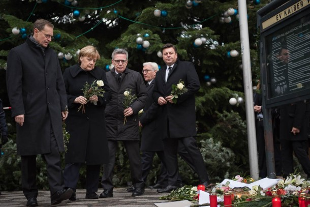 German Chancellor Angela Merkel (second from left), federal cabinet ministers and leading members of Berlin's government visited the scene at the Kaiser Wilhelm Memorial Church, where the deadly truck attack on a crowd at a Christmas market took place and laid one white rose each as a tribute to the victims of last Monday's carnage. Foto: Bundesregierung/Kugler.