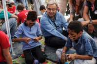 UN High Commissioner for refugees António Guterres sits among two young boys from Syria in a play area at the Moria Identification Centre, Lesvos. © UNHCR/A. Zavallis