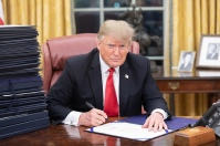 President Donald Trump is seen at his desk in the Oval Office. Sometimes he works hard, for the…bankers. (Official White House Photo by Shealah Craighead)